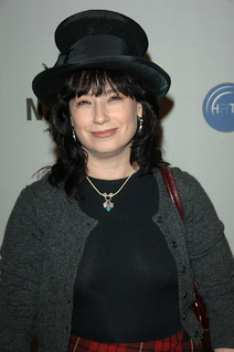 a photo of amy sherman-palladino smirking and wearing an oversized black velvet hat