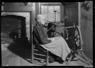 Another view of Mrs. Jacob Stooksbury, seated before a spinning wheel in her home. The creel in the background is used for measuring yarn by the hank, November 1933