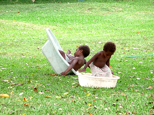 Ni-Vanuatu children playing in tubs in Efate Island in Vanuatu during a tour arranged by a Community Based Tourism Project.