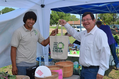 Crow Creek Fresh Food Initiative employee Wyatt Fleury at the Farmer's Market with Kevin Yellow Bird Steele.  With USDA support, a Farmers market is thriving in Ft. Thompson.