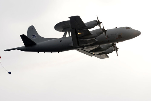 A P-3 Orion air drops a sealed capsule.