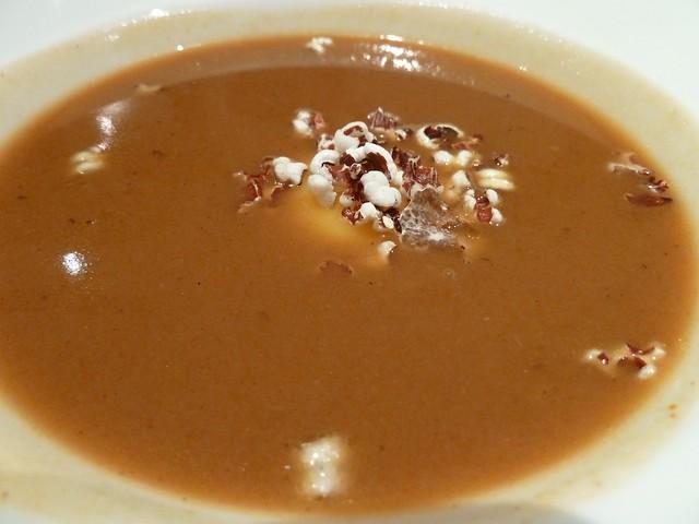 Sopas de ajo sobre yema de huevo con palomitas de arroz rojo y carpaccio de trufa blanca