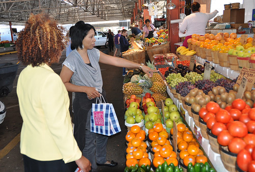 Food and Nutrition Service employees Jackie Garrett, right, and Angela Mathis, left, inquire about the price of grapes at a produce stand at the Dallas Farmers Market.