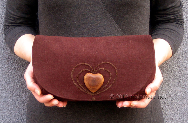 brown linen fabric clutch bag with olive wood heart and hand embroidered heart motif in hands