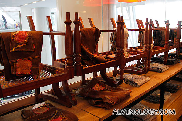 Inverted old wooden chairs to display their jeans collection