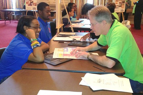 Volunteer & NCUF Deputy Executive Director Tom Candell counsels a teen on her budget after she visited all the booths at NCUF's Reality Fair at GAC.