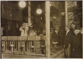 A photograph of 7-year-old Tommie Noonan demonstrating the advantages of the Ideal Necktie Form in a store window on Pennsylvania Avenue, near 13th Street, April 1912