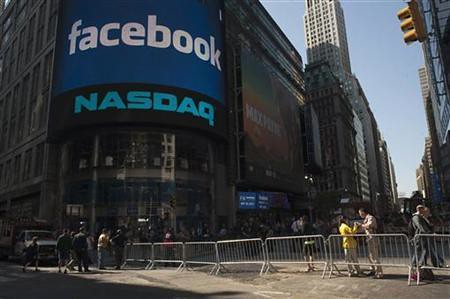 Pedestrians walk near the NASDAQ Marketsite at the start of the listing for Facebook in New York