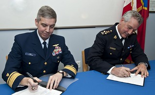 "Rear Adm. Dan Abel, commander of the 1st U.S. Coast Guard District and Assistant Commissioner Roger Brown, commanding officer of the Royal Canadian Mounted Police ""J"" Division sign a ""shiprider"" agreement at Station Eastport in Maine April 8, 2014. The agreement allows the Coast Guard and the RCMP to combat cross-border crime. Both sides complete joint training in each other's laws in Charleston, South Carolina. (U.S. Coast Guard photo by Petty Officer 3rd Class Ross Ruddell)"