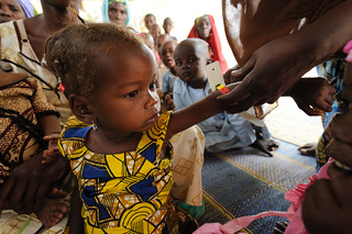 A child is screened for malnutrition using a Mid Upper-Arm Circumference (MUAC) measurement at a Save the Children...