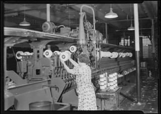 Textiles. Pacific Mills. Barber-Colman Automatic Spooler. Showing side of machine as operator takes off full cheese, April 1937