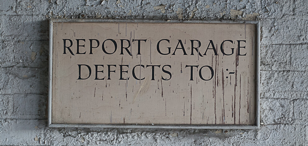 Photo depicting an old sign, stating one should report defects to...and no name was given.