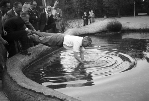 Man searching for lost item in fountain in 1954