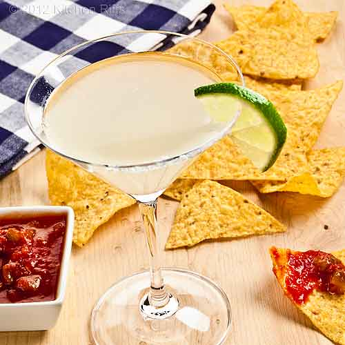 Classic Margarita Cocktail in Cocktail Glass, Tortilla Chips and Salsa in Background
