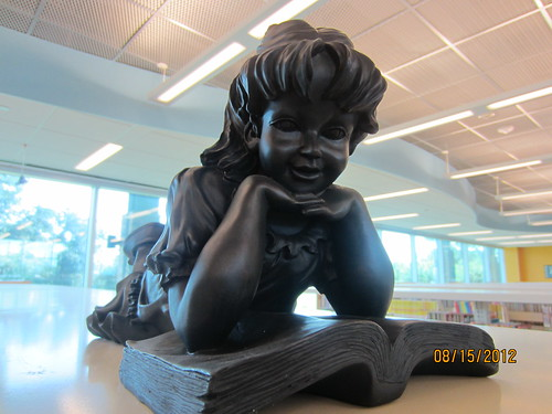 sculpture of a girl propped up on her elbows while reading a book