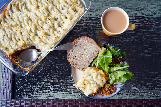 A tablescape from overhead: an almost-full pan of shepherd's pie angle across the upper-left of the small table, serving spoon resting where one scoop has been removed; a plate at center containing the scoop of shepherd's pie, a small green salad, and a slice of buttered bread; and a brimming mug of milky tea next to the plate.