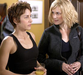 Two women, one with cropped brown hair and one with chin-length blonde hair, and both wearing dark tops, stand next to each other, holding drinks. The woman with brown hair is talking to someone off-camera, and the woman with blonde hair looks at her, concerned.
