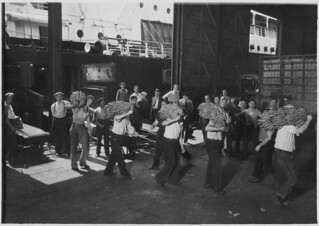 Longshoremen. This shows the prevailing method of transferring bananas from the end on the conveyor that carries them from the hold of the ship onto the dock, July 1937