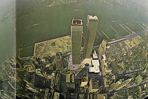 Cool aerial view of the World Trade Center twin towers going up, Battery Park City being filled-in, the old industrial Jersey City waterfront. New York. 1972.