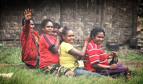 Papua province. Local girls are busy laying the hair
