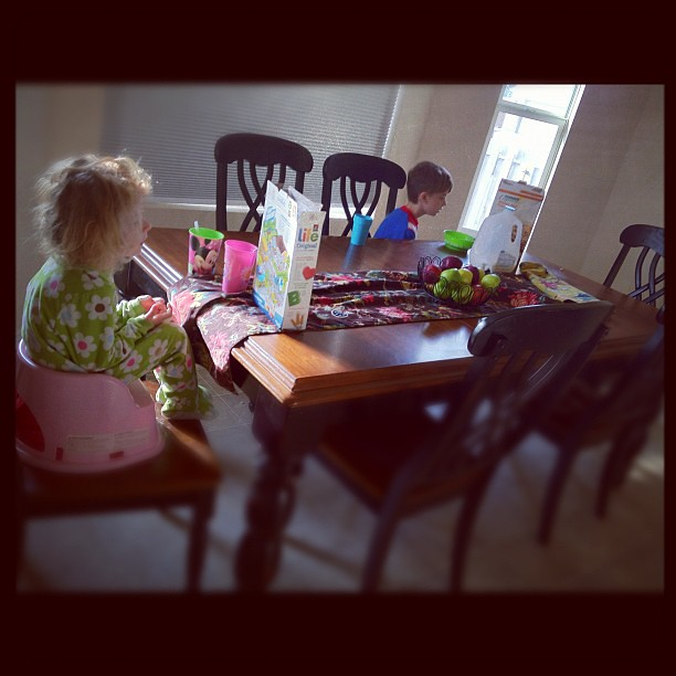 Sitting at the table reading a cereal box. #similarsiblings