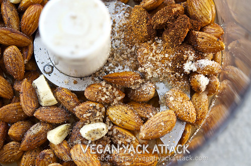 Close up shot of almonds, salt, and seasoning in a food processor