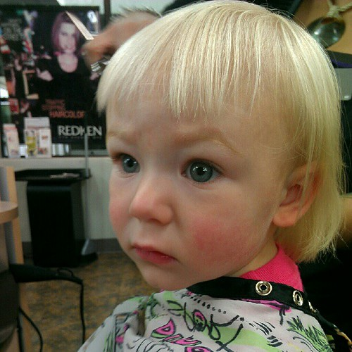 Big eyes during her first haircut.