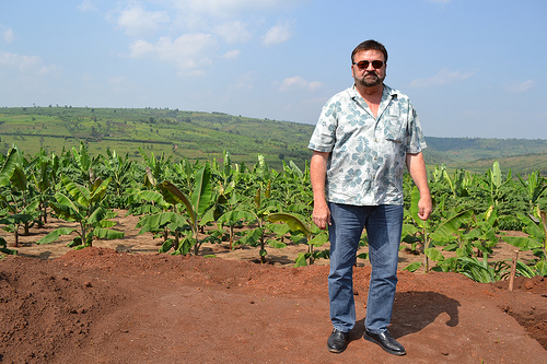 Forestry and Agricultural Investment Management (FAIM) entrepreneur and horticulturalist Steve Jones stands in front of his Rwandan farm. After an eye-opening agricultural trade mission to East Africa, Jones started FAIM to produce healthy, virus-free starter plants for Rwandan farmers to help boost their farm production, incomes and local food supply.  Using plant propagation techniques, FAIM has already helped Rwandan farmers increase crop production by 200-400 percent. Photo credit Mary L. Robbins.