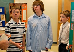 Three students discuss their project about World War II at Maine History Day.
