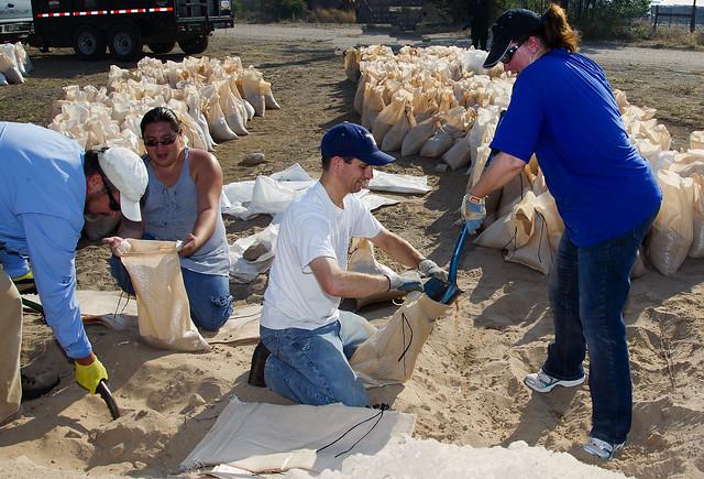 LANL employees Randy Erickson, left, and Louise Mendius, right, help fill sandbags at Santa Clara Pueblo.