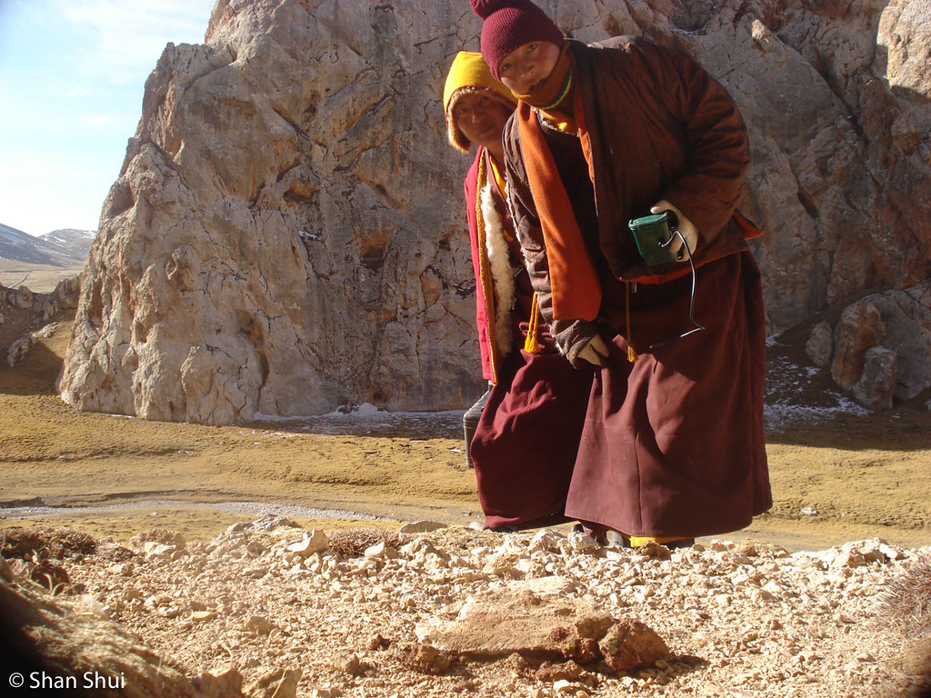 Two monks setting up and testing a camera trap in China's Qinghai province