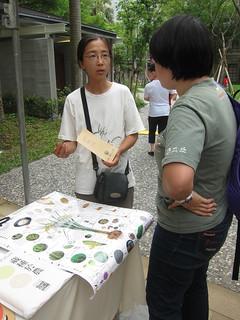 小農在攤位前向民眾解釋「藏種於農」的概念。攝影:詹嘉紋。