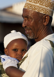 Father Carrying Baby With Coaled Eyelids During Maulidi, Lamu, Kenya