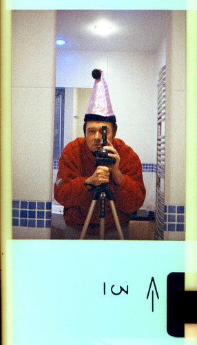 reflected self-portrait with Voigtlander Vitoret 110EL camera and Xmas hat from Poundland by pho-Tony