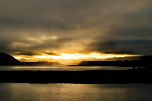 The sunrise over Lago Cucao with Chiloe National Park on the left shoulder of the slopes in background.  Photo courtesy of Michael Olwyler.
