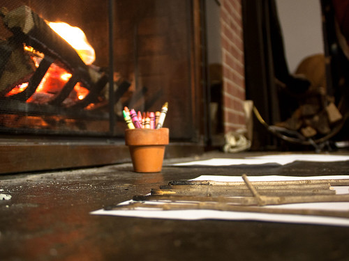 Photograph of crayons and charcoal pencils by a fireplace