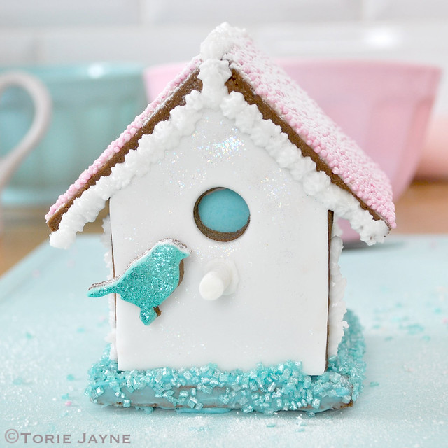 Sprinkling mini gingerbread bird house in confectioners sugar