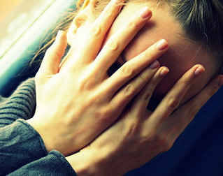 A young woman covering her face with both hands