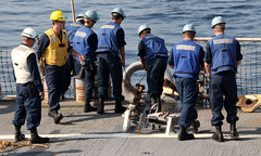 In this file photo, Boatswain's Mate 2nd Class Raymond M. Newton (in yellow), directs deck evolutions aboard USS Curtis Wilbur (DDG 54) as the ship gets underway from Yokosuka, Japan, Oct. 24, 2011. (U.S. Navy photo)