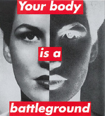 A print of a white woman's face divided in half, with one half portrayed in the negative. Red and white letters read Your Body is a Battleground