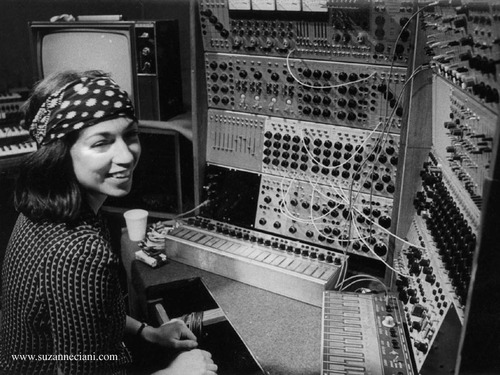 A black and white photograph of a 70s Suzanna smiling in front of a wall of knobs and wires