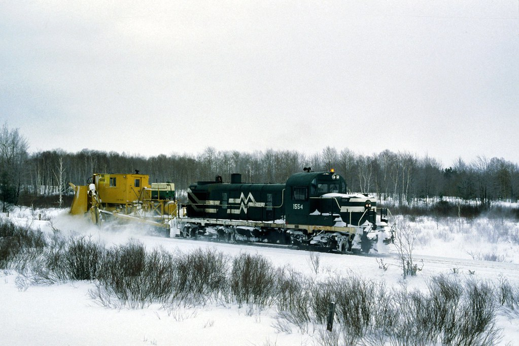 Michigan Northern 1554 with spreader 5002 south of Kalkaska 2-9-81. Photo by Neil Plagens.
