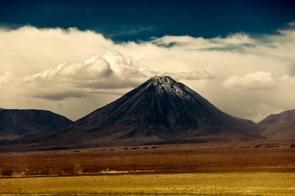 Una estela de polvo marca el rastro del convoy de vehículos mientras pasan delante del volcán nevado Licancabur en el desierto de Atacama en Chile. (Roberto Dam)