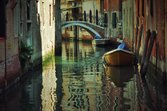 art(0.0), alley(0.0), street(0.0), vehicle(1.0), urban area(1.0), reflection(1.0), canal(1.0), boat(1.0), waterway(1.0), infrastructure(1.0),