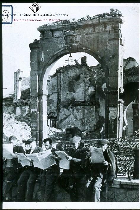 Leyendo el períódico ante las ruinas de Zocodover tras la Guerra Civil. Al fondo el Arco de la Sangre milagrosamente en pie