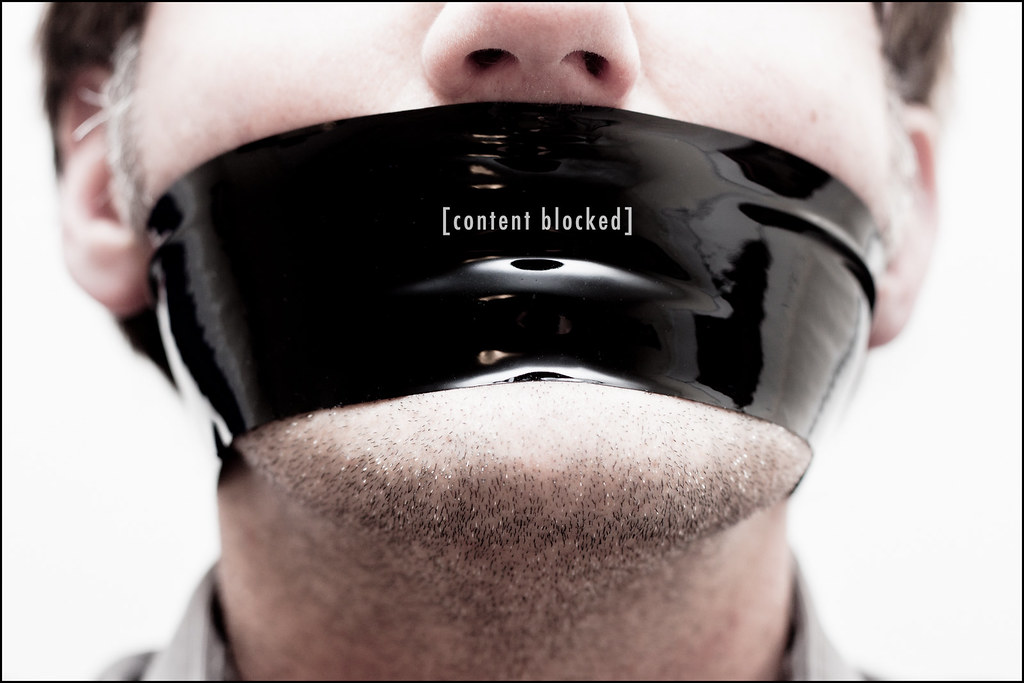 "Male with black tape across mouth bearing words ""content blocked"""