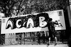 متظاهر يرش جرافيتي مناهض لأوغاد الشرطة خلال مسيرة الجيزة