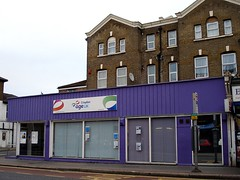 "A colour photo of the same shopfront as above from a different angle.  Blinds have been drawn across the windows from inside.  The surround is painted purple, and a sign reads ""Croydon Age UK""."