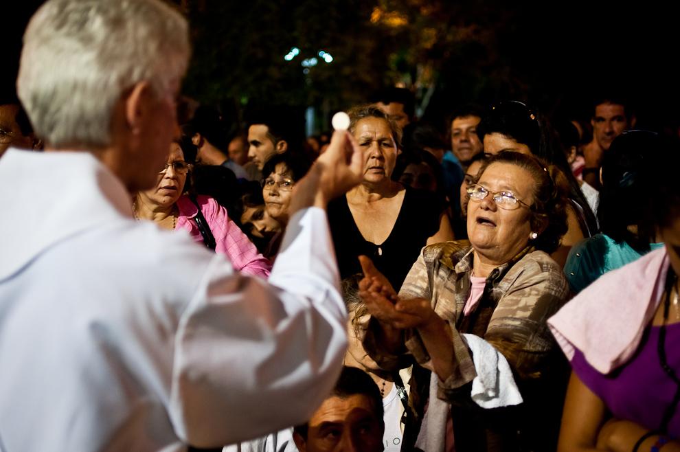 Una señora extiende su mano para recibir la hostia consagrada durante la santa comunión, durante la misa de la medianoche que se realiza en la plaza principal, frente a la Basílica. (Elton Núñez)