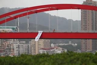 反對新建淡北快速道路,環團在關渡大橋垂下七公尺長「Save淡水河岸」的巨型抗議布條照片。(綠色公民行動聯盟提供)